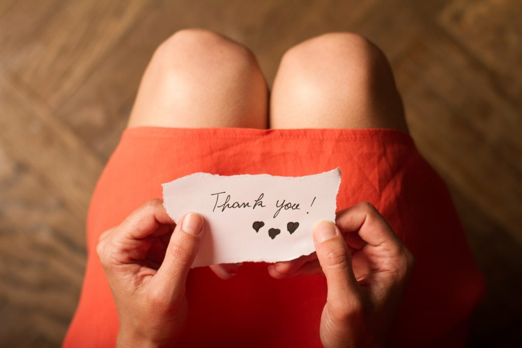 Top view of a woman with pink dress holding a thank you note in her hand